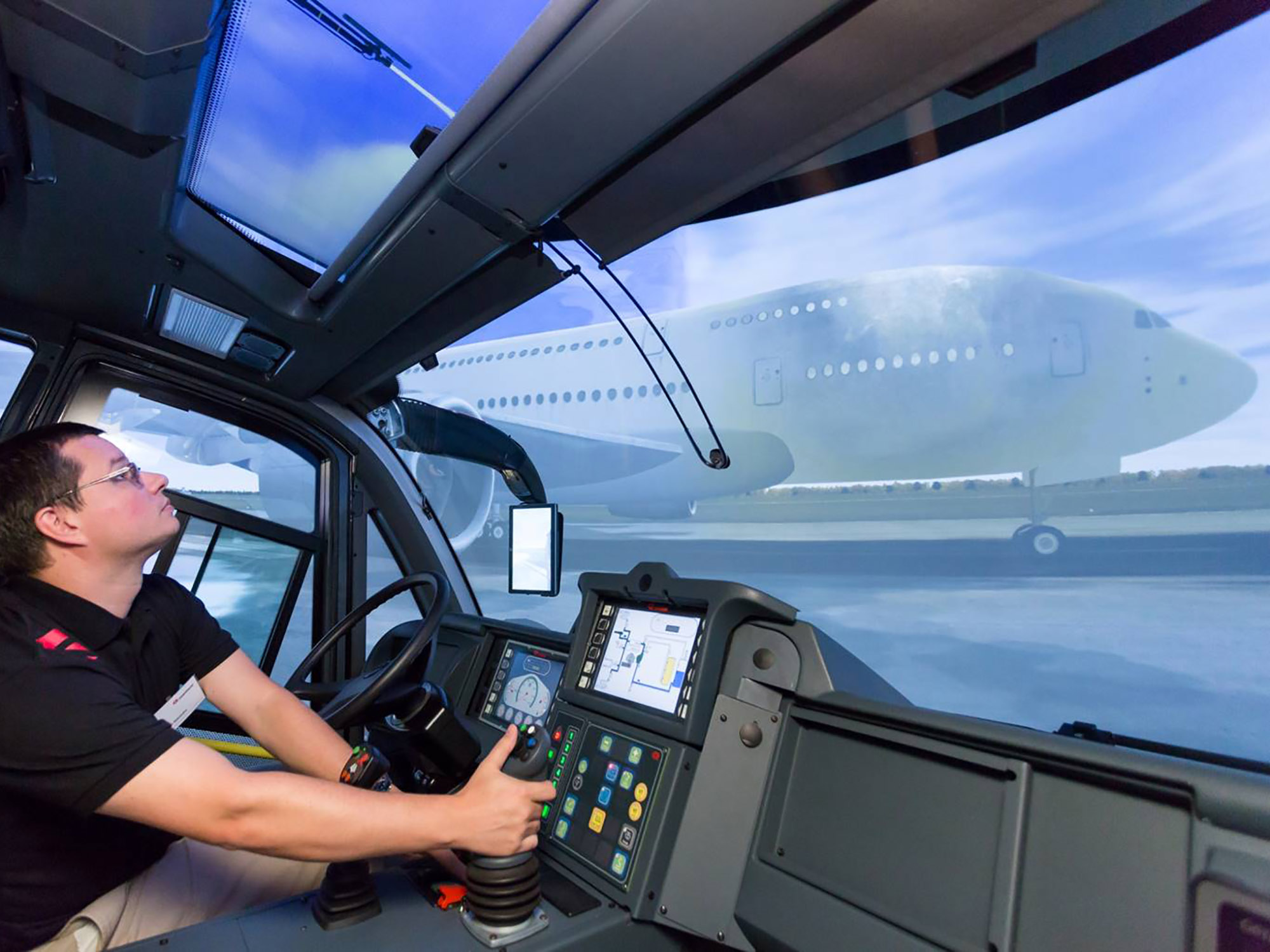 A trainee is operating the HRET to extinguish an A-380 interior fire from inside a full cabin ARFF simulator.